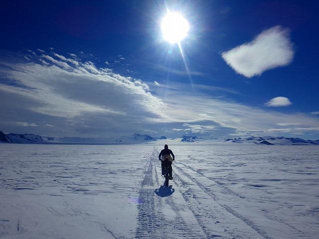 南極の輝く雪面を走る大島さん